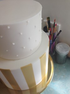 Piped royal icing dots added to the top tier contrasts the stripes